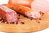 Tasty sausage on chopping board close-up — Stock Photo
