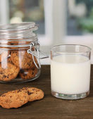 Glass of milk with cookies on wooden table on windows background close-up — Stock Photo