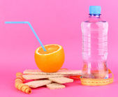 Ripe oranges, loafs and bottle of water as symbol of diet on pink background — Stock Photo