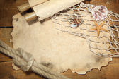 Old paper, fishing net and rope on wooden table — Stock Photo