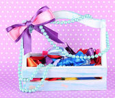 Bows in wooden box on color background — Stock Photo