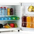 Mini fridge full of bottles of juice, soda and fruit isolated on white - Stock Photo