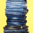 Stock Photo: Many jeans stacked in pile on yellow background