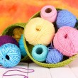 Colorful yarn for knitting in green basket on white wooden table on colorful background — Stock Photo #14315189