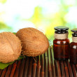 Coconut oil in bottles with coconuts on green background — Stock Photo #14315211