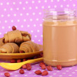 Delicious peanut butter with cookies on purple background with polka dots - Stock Photo