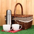 Metal thermos with cups and basket on grass on wooden background — Stock Photo #14316395