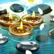 Spa stones with flowers and candles in water - Stock Photo