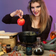 Halloween witch preparing poison soup in her cauldron on color background — Stock Photo #14317659