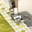 Stock Photo: Closeup of sewing machine working part with green cloth