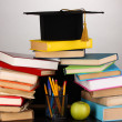 Books and magister cap against school board on wooden table on grey background - 图库照片