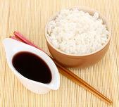 Bowl of rice and chopsticks on bamboo mat — Stock Photo