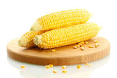 Fresh corn on wooden cutting board, isolated on white — Stock Photo