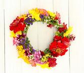 Guirnalda de flores de verano hermoso, sobre fondo blanco de madera — Foto de Stock