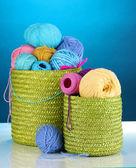 在蓝色背景上的绿色篮子编织七彩纱 — 图库照片
