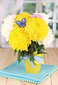 Beautiful chrysanthemum in pail on wooden table on window background — Foto de Stock