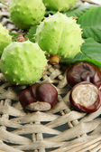 Chestnuts with leaves on wicker background — Stock Photo