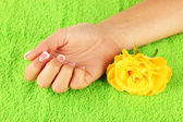 Yellow rose with woman's hand on green terry towel, close-up — Foto de Stock