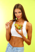 Beautiful young woman with salad, on green background — Stock Photo