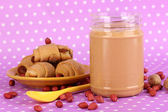 Delicious peanut butter with cookies on purple background with polka dots — Stock Photo