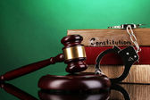 Gavel, handcuffs and books on law on green background — Stock Photo