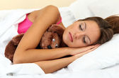 Young beautiful woman sleeping with fluffy bear in bed — Stock Photo