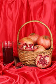 Ripe pomegranates on basket with glass of pomegranate juice on red cloth background — Stock Photo