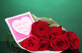 Beautiful bouquet of red roses with valentine on green background — Stock Photo