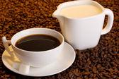 Une tasse de café fort et le gros plan de grains de café crème — Photo
