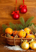 Christmas composition in basket with oranges and fir tree, on wooden background — Zdjęcie stockowe