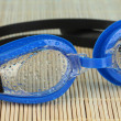 Blue swim goggles with drops on a bamboo pad — Stock Photo #14333085