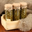 Glass jars with tinned capers on sack background close-up — Stock Photo #14333249