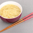 Asian noodles in bowl on grey mat - Stock Photo
