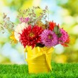 Bright yellow bucket with flowers on green background — Stock Photo #14333415