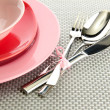 Pink empty plates with fork, spoon and knife on a grey tablecloth - Stock Photo