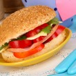 Appetizing sandwich on color plate close-up on wooden table on window background - Stock Photo