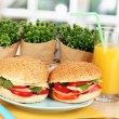 Appetizing sandwiches on color plate on wooden table on window background - Stock Photo