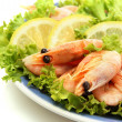 Boiled shrimps with lemon and lettuce leaves on plate, isolated on white - Stock Photo