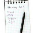 Stock Photo: Shopping list in a notebook on white background close-up