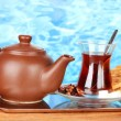Glass of Turkish tea and kettle on color background - Stock Photo