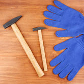 Hammers and gloves on wooden background — Stock Photo