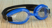 Blue swim goggles with drops on a bamboo pad — Stock Photo