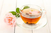 Cup of tea with rose on white wooden table — Stock Photo