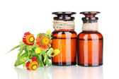Medicine bottles and flowers isolated on white — Stock Photo