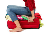 The girl is trying to close suitcase crammed on white background — Stock Photo