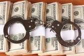 Handcuffs on the packs of dollars on wooden table close-up — Stock Photo