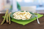 Plate with coleslaw and asparagus on wooden table on room background — Stock Photo