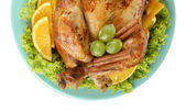 whole roasted chicken with lettuce, grapes, oranges and spices on blue plate on white background close-up — Stock Photo