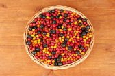 Colorful autumn berries on wicker mat on wooden background close-up — Stock Photo