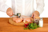 Chef beats meat on wooden table — Stock Photo